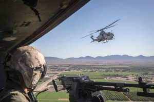 Picture of Marine AH-1Z Cobra and F-35B Lighting II flying over farmlands. Marine in the foreground with weapon